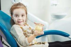 Jeux d'enfant avec la mâchoire humaine artificielle dans la chaise de dentiste images libres de droits