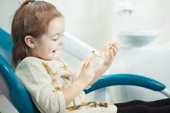 Jeux d'enfant avec la mâchoire humaine artificielle dans la chaise de dentiste photos stock