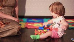 Jeux d'enfant avec un jouet sur le plancher clips vidéos