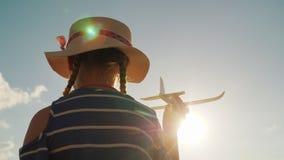 Jeux d'enfant mignons avec une arme à feu de jouet Dans les rayons du soleil, la vue arrière Le bébé rêve le concept Image stock