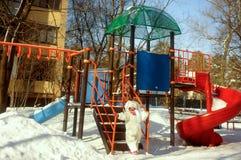Jeux d'enfant sur un terrain de jeu neigeux Photographie stock libre de droits