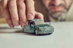 Jeux d'une cinquantaine d'années d'homme avec la voiture minable de jouet Photographie stock libre de droits