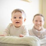 Jeux de bébé avec la mère sur le divan Photographie stock libre de droits