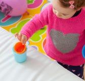 Jeux de bébé d'enfant en bas âge avec les tasses colorées Photographie stock