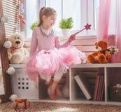Jeux de fille avec la baguette magique magique Photo stock