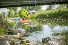Jeux de garçon avec de l'eau près d'un lac Images libres de droits