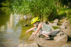 Jeux de garçon avec de l'eau près d'un lac Photos stock
