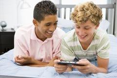 jeux de garçons écoutant le vidéo d'adolescent Images libres de droits