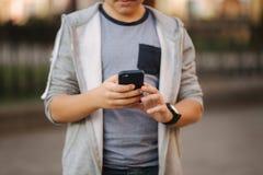 Jeux de jeu d'adolescent au téléphone portable dehors image stock