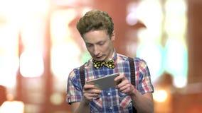 Jeux de l'adolescence drôles de garçon à son téléphone intelligent banque de vidéos
