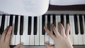 Jeux de l'adolescence de fille sur le clavier du piano numérique Plan rapproché banque de vidéos