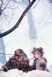 Jeux de petit garçon et de fille à l'arrière-plan de forêt de neige de studio Photographie stock