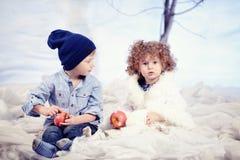 Jeux de petit garçon et de fille à l'arrière-plan de forêt de neige de studio Image stock