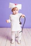 Jeux de petite fille dans l'infirmière d'hôpital Image libre de droits