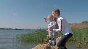 Jeux de plein air, jeune mère avec le petit fils jetant de petits cailloux dans l'eau se tenant sur la berge pendant des vacances clips vidéos