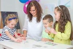 Jeux de professeur avec des enfants Photographie stock