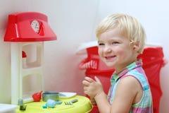 Jeux drôles de fille d'élève du cours préparatoire avec la cuisine de jouet Photo libre de droits