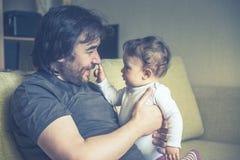 Jeux heureux de père avec son bébé à la maison Photographie stock libre de droits