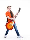 Jeux mignons de fille sur la guitare électrique. photo stock