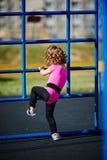 Jeux mignons de petite fille sur le terrain de jeu Photographie stock libre de droits