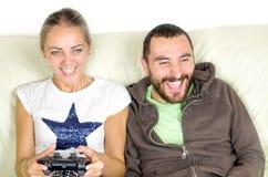 Jeux vidéo de jeu de couples - l'homme encourage son amie tandis que pla Photos stock