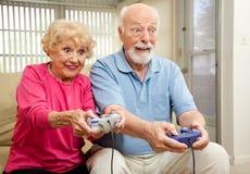 Jeux vidéo aînés de pièce de couples Image stock