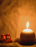 Jewel and candle. Jewel and round candle on fur Royalty Free Stock Photo