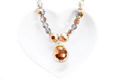 Jewel necklace on heart shaped saucer Stock Image