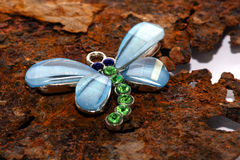 Jeweled butterfly pendant. Closeup of a jeweled butterfly pendant on a rusty metal surface Royalty Free Stock Image