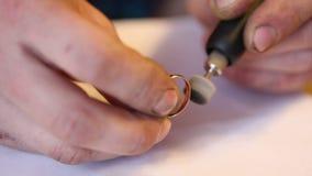 Jeweler που γυαλίζει το χρυσό δαχτυλίδι με τη βοήθεια φιλμ μικρού μήκους