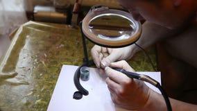 Jeweler που γυαλίζει το χρυσό δαχτυλίδι με φιλμ μικρού μήκους