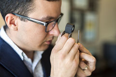 Jeweler που εξετάζει το διαμάντι μέσω του loupe Στοκ Εικόνα