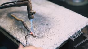 Jeweler connects chain links by special welding closeup
