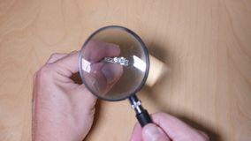Jeweler Examines Diamond Ring Under Magnifying Glass. 8617 A jeweler examines a diamond ring under a magnifying glass stock footage