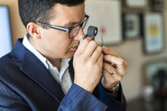 Jeweler looking at diamond through loupe Royalty Free Stock Photography