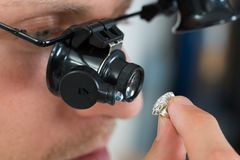 Jeweler Looking Ring With Loupe. Close-up Of Jeweler Looking Ring Through Magnifying Loupe Royalty Free Stock Photo