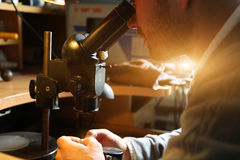 Jeweler looking at the ring through microscope Royalty Free Stock Photography