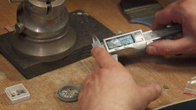 Jeweler measures gems on the workshop bench. Caucasian jeweler measuring gems on the workshop bench. Close up of male hands taking gem by digital caliper. Camera stock video footage