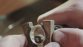 Jeweler polishes the gold ring holding the ring in one hand and the polishing tool in the other. The ring is located on stock video