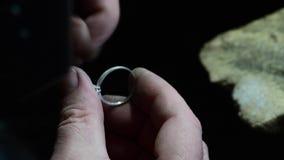 Jeweler polishing golden wedding ring. Craft jewelery. Silver ring