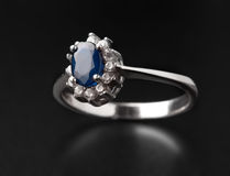 Jeweler ring. With a dark blue stone on black background Stock Photography