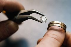 Jeweler tries on a precious stone in a gold blank for the future of the ring. Close-up stock photo