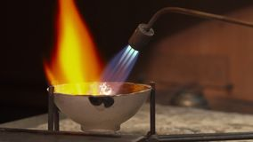 Jeweler uses gas torch. Professional jeweler using gas torch for melting precious metal. Close up of handlers tilting crucible to the sides. Jewelry specialist Stock Photography