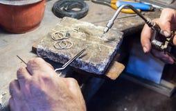 Jeweler using a gas - oxygen welding torch. Jeweler welding a silver chain with a mini gas - oxygen torch welder stock image