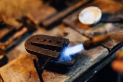 Jeweler using tourch to heat welding tools Royalty Free Stock Image
