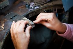 Jeweler working with needle file gold ring in jewellery worksho. Jeweler working with a needle file a gold ring on an old workbench in authentic jewellery stock photos
