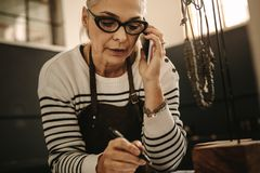 Jeweler writing clients design requirements. Portrait of senior female jeweler making note and talking on smart phone. Mature woman jewelry designer talking with stock images