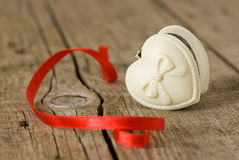 Jewelery box in heart shape. On old wooden table stock photography