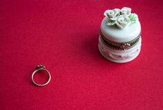 Jewelery box and ring. On red background Royalty Free Stock Photo