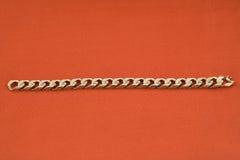 Jewelery gold bracelet. Red background Stock Photo